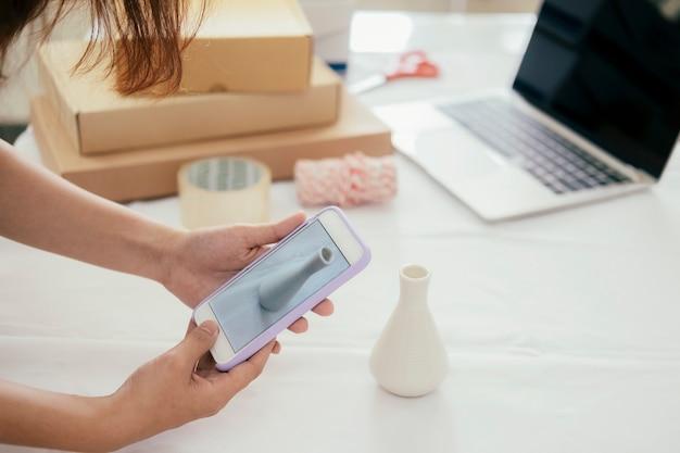 El propietario del vendedor en línea toma una foto del producto para cargarlo en la tienda en línea del sitio web.