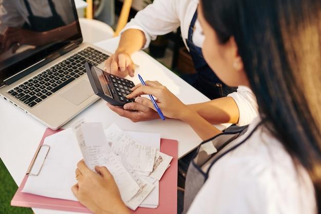 Propietarios jóvenes de cafés que controlan facturas y cheques de pago al calcular ingresos y gastos