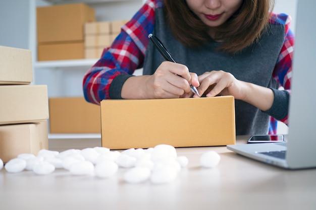 Los propietarios de pequeñas empresas están escribiendo nombres para prepararse para entregar paquetes a los clientes. pequeñas empresas que venden en línea y solicitan productos en línea