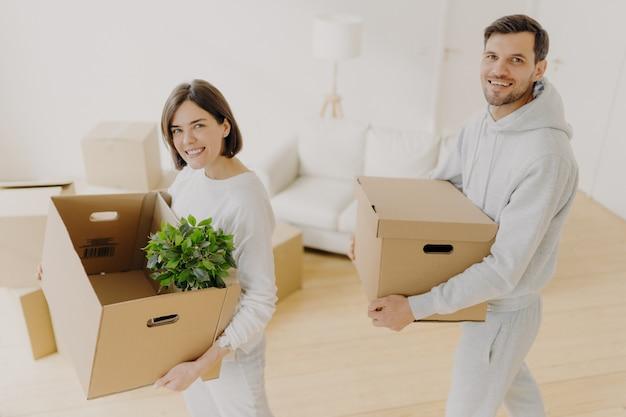 Los propietarios positivos, hombres y mujeres, posan con sus pertenencias personales en cajas de cartón, reubicación
