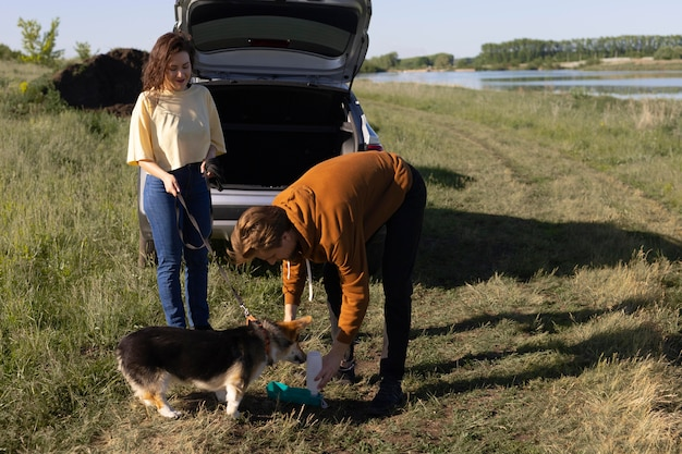 Propietarios de tiro completo dando agua para perros