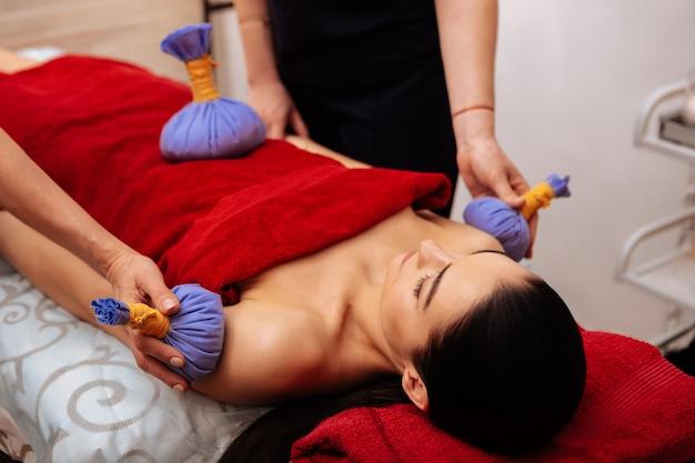 Proporcionar sesión relajante. mujer joven pacífica acostada en la cama de masaje mientras los maestros dan su procedimiento con bolsas de hierbas azules