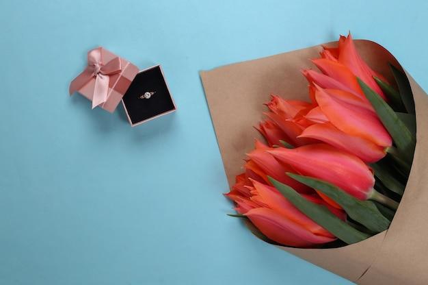 Propuesta de matrimonio. ramo de tulipanes, anillo de oro con diamante en caja de regalo en azul