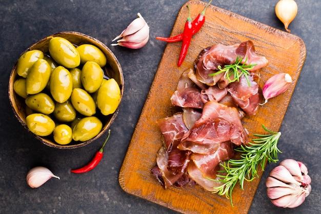 Prosciutto italiano crudo o jamón con especias, aceitunas, romero