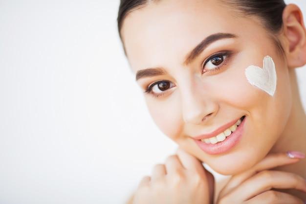 Protección de la piel. bella modelo aplicando tratamiento de crema cosmética en su rostro.