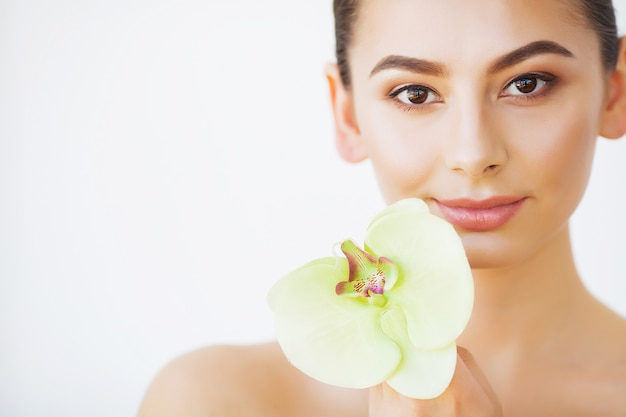 Protección de la piel. belleza de mujer, maquillaje y cuidado de la piel de la cara, flor de orquídea de niña