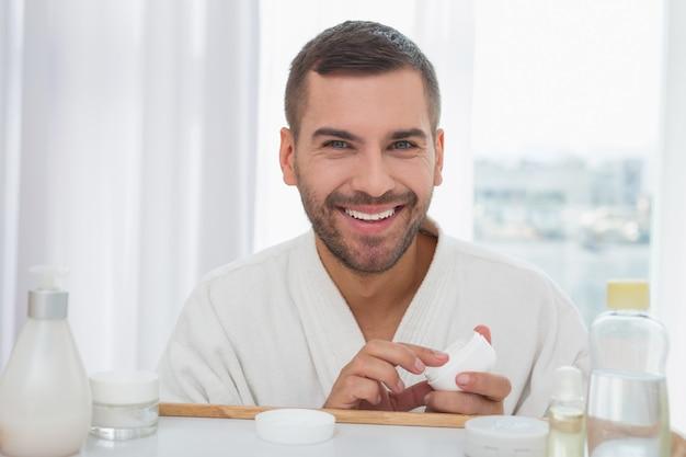 Protección de la piel. buen hombre alegre sosteniendo una botella de crema mientras se preocupa por su piel