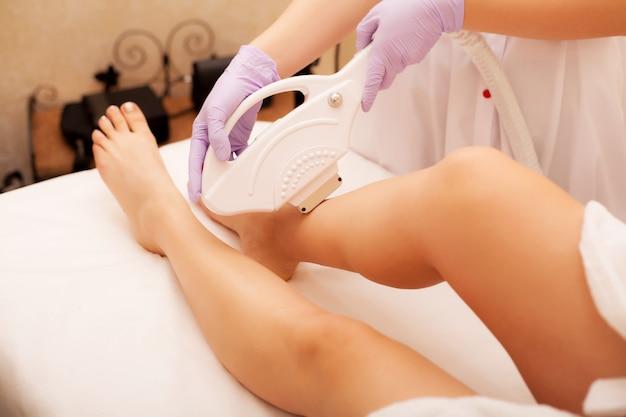 Protección de la piel. depilación en las piernas, procedimiento con láser en la clínica. esteticista elimina el vello de hermosas piernas femeninas usando un láser