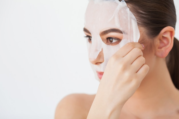 Protección de la piel. hembra joven que quita la máscara de la piel facial. mujer, belleza, cara