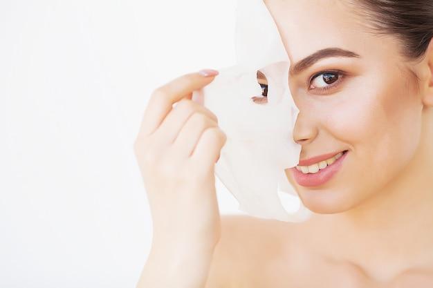 Protección de la piel. hermosa chica con máscara de sábana en la cara