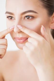 Protección de la piel. hermosa mujer apretando espinillas en el espejo del baño