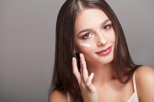 Protección de la piel . hermosa mujer con crema de manos, loción en sus manos.