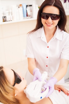 Protección de la piel. mujer adulta con depilación láser en salón de belleza profesional