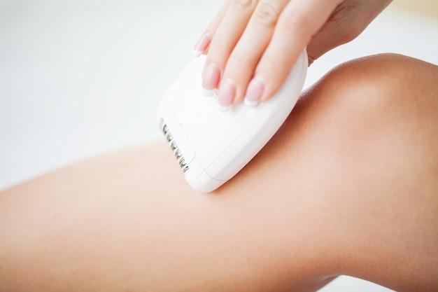 Protección de la piel. mujer afeitándose las piernas en el baño