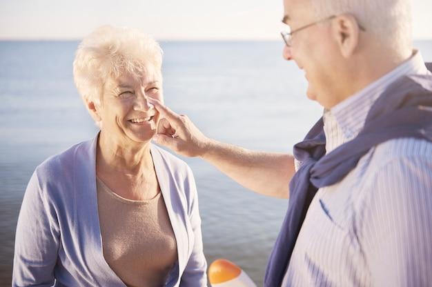 Protección solar en la playa. pareja senior en la playa, la jubilación y el concepto de vacaciones de verano