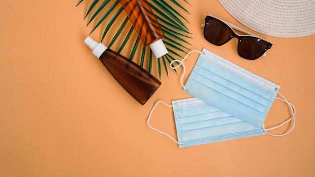 Proteccion solar. sombrero de paja de playa, gafas de sol, crema de protección spf, mascarilla médica. accesorio de playa. viajes de verano en concepto de cuarentena por coronavirus.