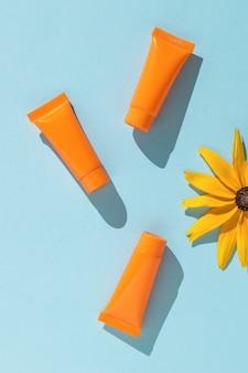 Protector solar y una flor brillante sobre un fondo azul. endecha plana.