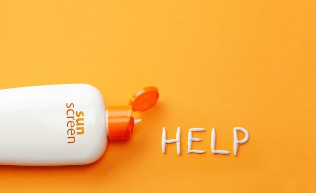 Protector solar sobre fondo naranja botella de plástico de protección solar y crema blanca en ayuda