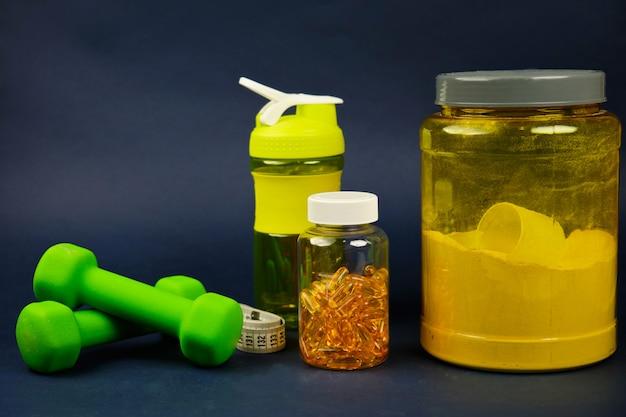 Proteína en un frasco amarillo, agitador de plástico, pesas verdes y un frasco de omega 3