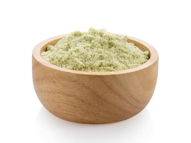Proteína de suero en un recipiente de madera sobre una superficie blanca.