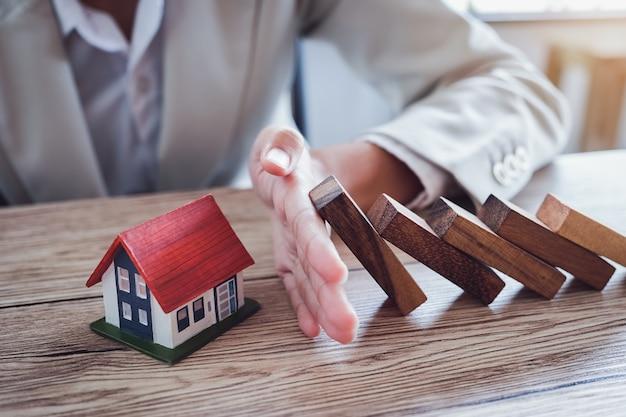 Proteja la casa de caerse sobre los bloques de madera, el seguro y el concepto de riesgo.