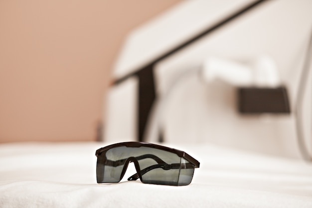 Proteja las gafas en los ojos y el dispositivo de belleza para el tratamiento de la piel en el fondo. salón de belleza spa.