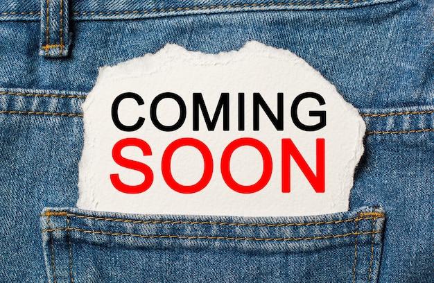 Próximamente en la pared de papel rasgada en el concepto de negocios y finanzas de jeans