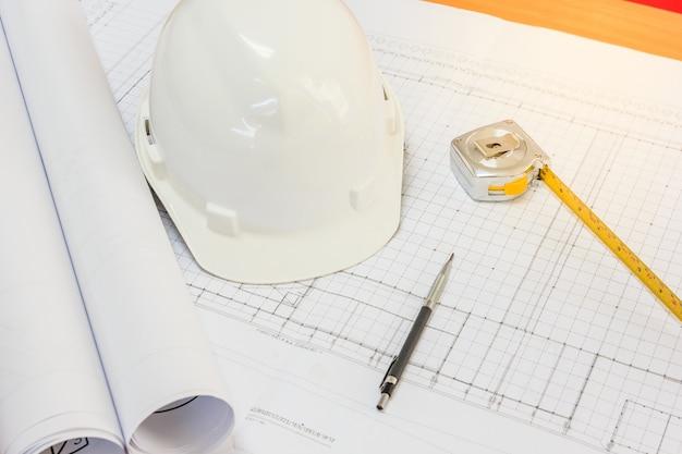 Proyecto arquitectónico, planos, rollos de planos, bolígrafo y cinta métrica sobre planos.