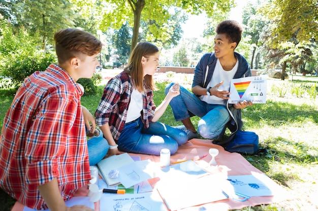 Proyecto de arte. equipo de estudiantes universitarios creativos inteligentes que trabajan en su proyecto de arte mientras pasan su tiempo en la naturaleza