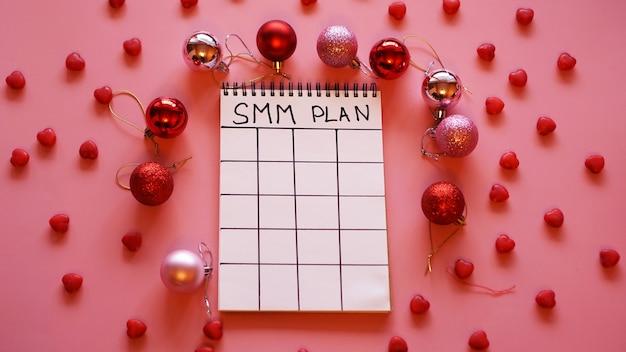 Proyecto freelance. plan smm en blanco. hoja blanca sobre un fondo rosa festivo con bolas rojas de navidad y dulces en forma de corazones