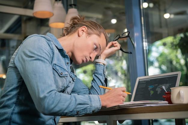 Proyecto serio. buen hombre inteligente quitándose las gafas mientras está cansado de trabajar en un proyecto serio