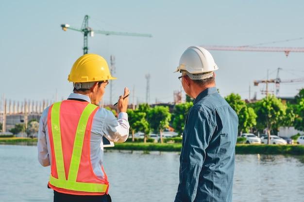 Proyecto de sitio de construcción de dos ingenieros hablando plan