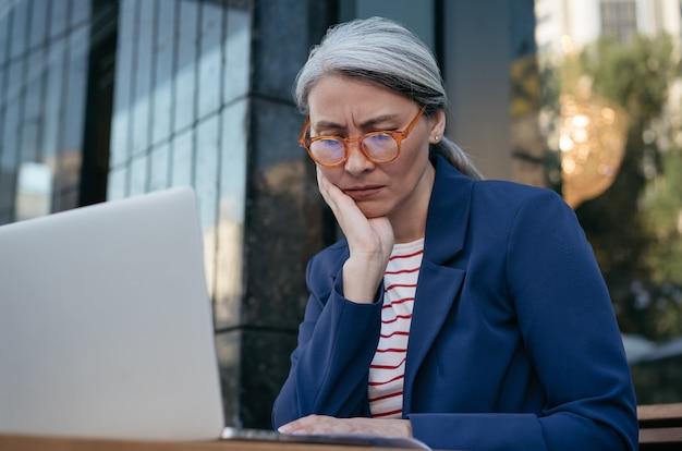 Proyecto de trabajo de empresaria asiática cansada, usando laptop, buscando información
