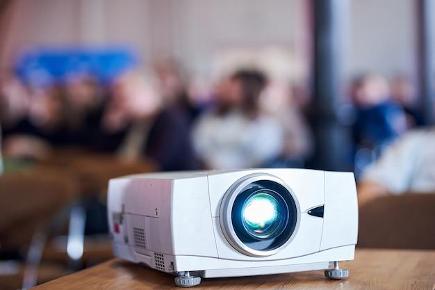 Proyector multimedia de primer plano con fondo borroso de personas