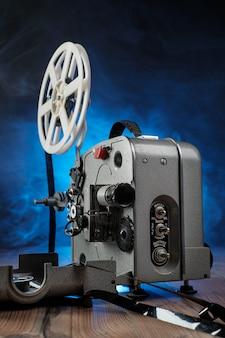 Proyector de películas con la película en el piso de madera.
