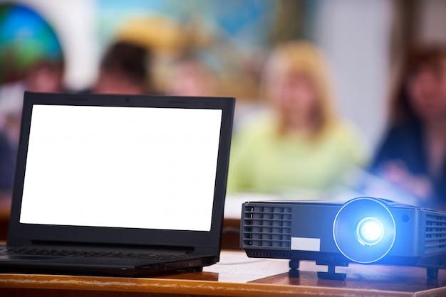 Proyector de trabajo en la sala de conferencias. portátil con pantalla en blanco. gente borrosa en el fondo.