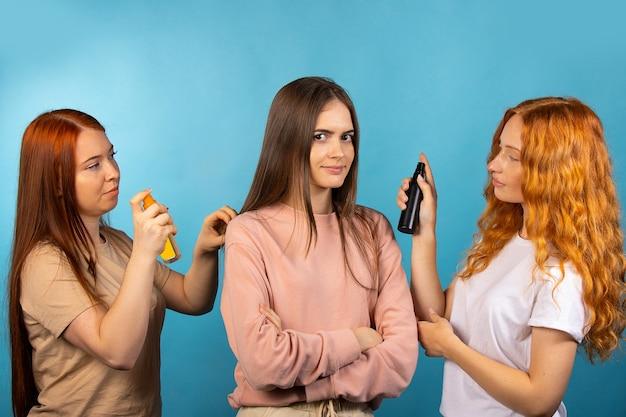 Prueba de aroma. dos chicas consultoras están probando nuevas fragancias en una tercera chica. probador de productos de peluquería. foto en pared azul.
