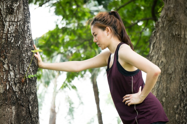 Se prueba y descansa a una mujer del deporte asiático después de correr en el parque