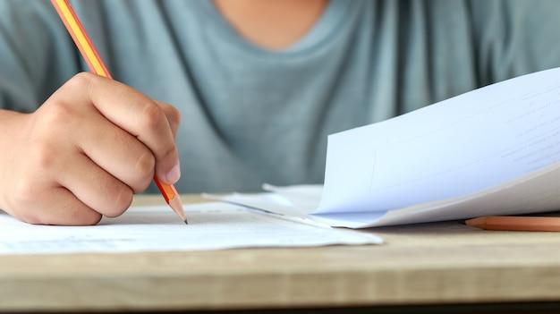 Prueba de educación en la universidad o el concepto de escuela secundaria estudiante de manos sosteniendo un lápiz para probar exámenes