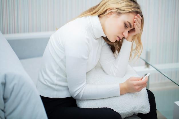 Prueba de embarazo positiva. mujer joven que se siente deprimida y triste después de mirar el resultado de la prueba de embarazo en casa