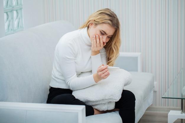 Prueba de embarazo positiva, mujer joven que se siente deprimida y triste después de ver el resultado de la prueba de embarazo en casa