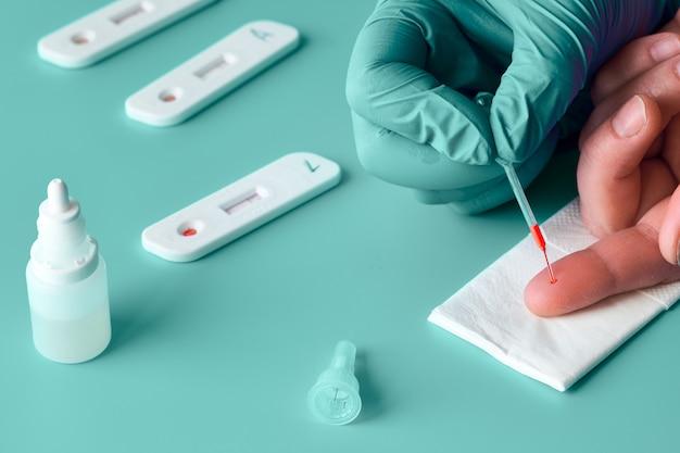 Prueba express covid-19 para anticuerpos igm e igg contra nuevos coronavirus sars-cov-2, covid-19. la mano de la enfermera en guante de nitril recoge la sangre del paciente con una pipeta. gren fondo menta turquesa, espacio de copia.