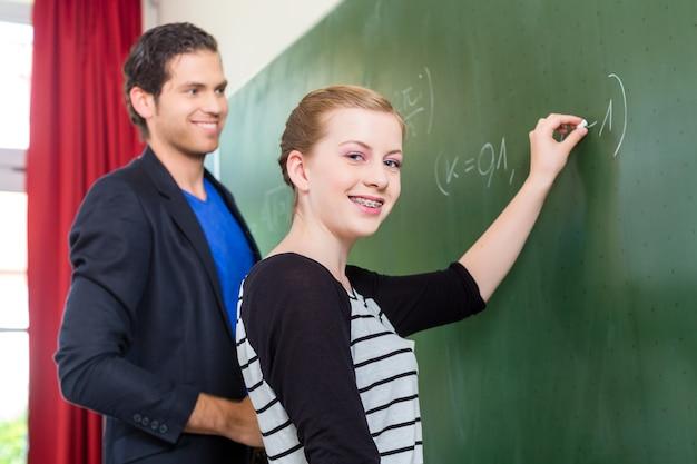 Prueba del maestro mientras los estudiantes de las lecciones o la niña en la escuela frente a la clase en la pizarra o pizarra o pizarra en matemáticas