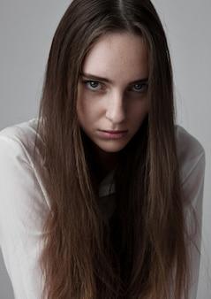 Prueba modelo con modelo de moda joven y bella con el pelo largo con camisa blanca sobre fondo gris
