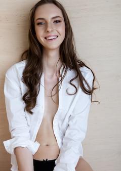 Prueba de retrato modelo con modelo de moda hermosa joven con camisa blanca sobre fondo de madera contrachapada. hermosa sonrisa