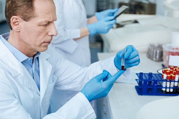 Prueba de sangre. foto de perfil de un médico competente mientras sostiene un vaso de prueba con sangre y va a probarlo mientras está sentado en el laboratorio