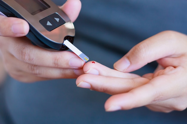 Pruebe la glucosa en sangre para la diabetes en una mujer embarazada con glucómetro