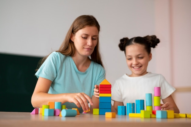 Psicóloga ayudando a una niña en la terapia del habla
