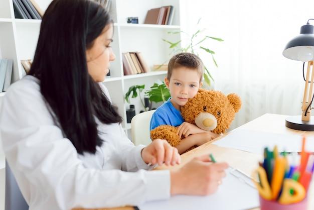 Psicóloga femenina calmante niño lindo en office