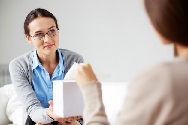 Psicóloga ofreciendo un pañuelo de papel